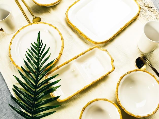 Piatti bianchi con foglia tropicale