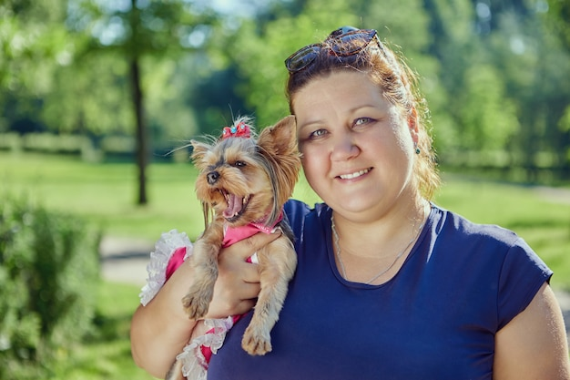 La donna bianca plus size tiene in braccio lo yorkshire terrier