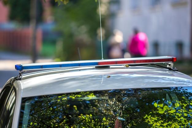 L'incrociatore bianco del volante della polizia con le luci di emergenza ha parcheggiato sulla via soleggiata dell'estate. sicurezza e controllo nella vita moderna.