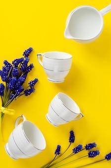 Set caffè o tè in porcellana bianca, vaso con latte, fiori muscari su giallo