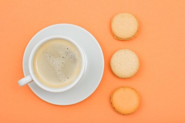 Tazza di caffè in porcellana bianca sul piattino e deliziose torte di macarons su sfondo color pesca. vista dall'alto