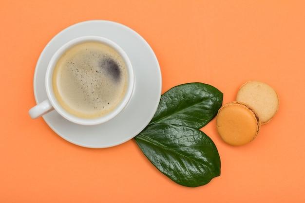 Tazza di caffè in porcellana bianca sul piattino e deliziose torte di macarons con foglie verdi su sfondo color pesca. vista dall'alto