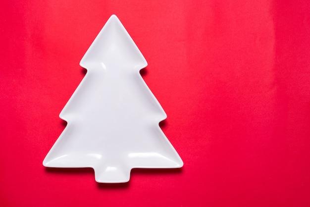 Piatto di porcellana bianca a forma di albero di natale su sfondo rosso