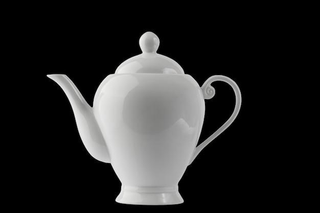 I dettagli del set da tè in porcellana bianca si isolano su uno sfondo nero