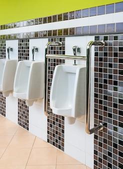 Orinatoi in porcellana bianca per storpi e anziani nei bagni pubblici