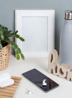 Mockup di cornice per poster bianco con gadget moderni, bottiglia isolata sul muro grigio