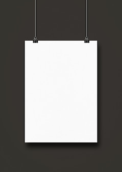 Poster bianco appeso a una parete nera con clip.