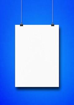 Poster bianco appeso a una parete blu con clip.