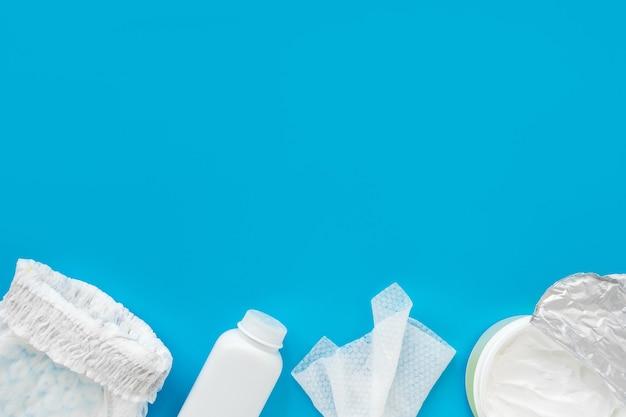 Polvere bianca, pannolino, crema, tovagliolo su sfondo blu, flatley, vista dall'alto, copia spazio, mock up. igiene del bambino, sfondo per i neonati.