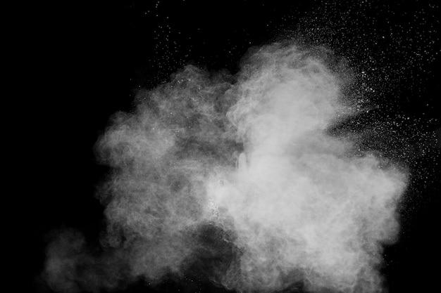 Nuvola bianca di esplosione della polvere contro fondo nero spruzzata bianca delle particelle di polvere.