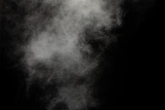 Nuvola di esplosione di polvere bianca su sfondo nero spruzzata di particelle di polvere bianca.