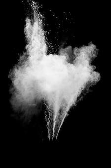 Esplosione di polvere bianca isolata su sfondo nero. spruzzata di particelle di polvere bianca. festival di holi di colore.