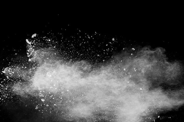 Esplosione di polvere bianca isolata su fondo nero spruzzata bianca delle particelle di polvere.