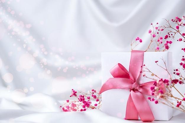 Scatola regalo bianca con nastro rosa e piccoli fiori rosa su sfondo bianco in tessuto di seta. biglietto di auguri per le vacanze. copia spazio. diserbo compleanno san valentino festa della mamma donna