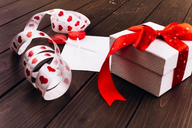 La casella bianca presente con il nastro rosso si leva in piedi sulla scheda vuota sulla tabella di legno