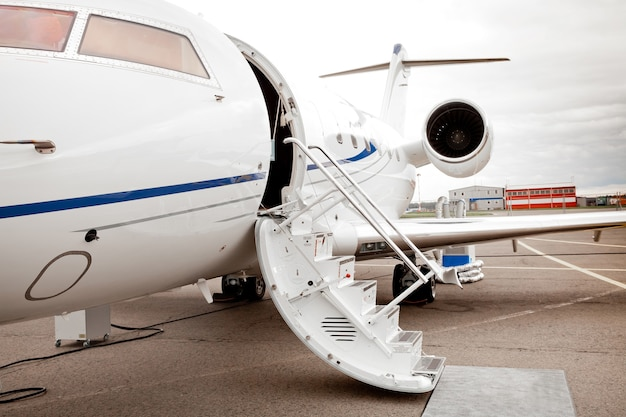 Jet privato bianco di affari e scaletta aperta all'aeroporto
