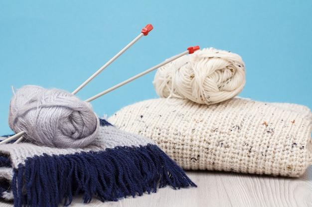 Pullover bianco, sciarpa e matasse di filo con ferri da maglia in metallo su tavole grigie e sfondo blu. concetto di maglieria.