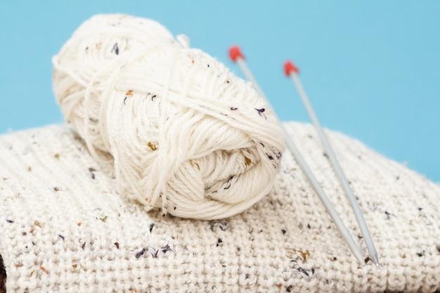 Pullover bianco e matassa di filo con ferri da maglia in metallo su tavole grigie e sfondo blu. concetto di maglieria. profondità di campo.