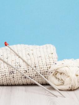 Pullover bianco e matassa di filo con ferri da maglia in metallo su tavole grigie e sfondo blu. concetto di maglieria.