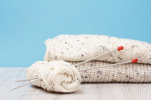 Pullover bianchi e matasse di filo con ferri da maglia in metallo su tavole grigie e sfondo blu. concetto di maglieria.
