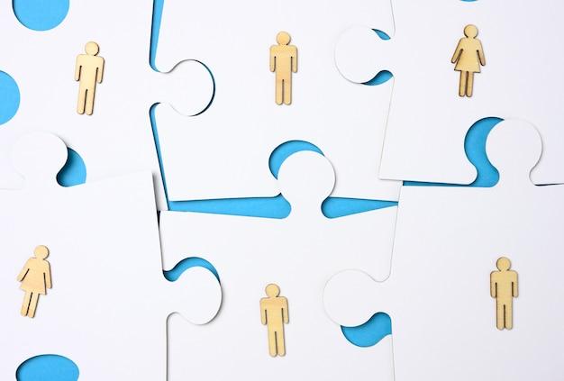 Puzzle bianchi e uomini di legno. concetto di reclutamento, compatibilità del team, individualità di ciascuno