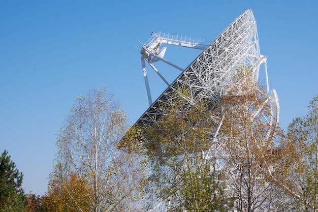 Grande parabola satellitare del radiotelescopio bianco su uno sfondo di cielo azzurro e alberi