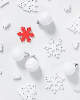 Bagattelle e fiocchi di neve bianchi e rossi di natale sulla vista bianca del piano d'appoggio. composizione invernale monocromatica con decorazioni natalizie