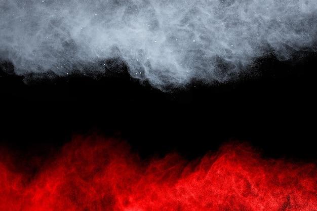 Esplosione di polvere di colore bianco e rosso su sfondo nero