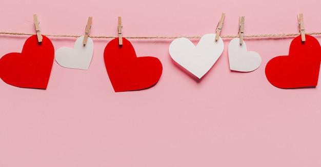 Perno di cuore bianco e rosso su una fune su sfondo rosa isolato, amore e concetto di san valentino