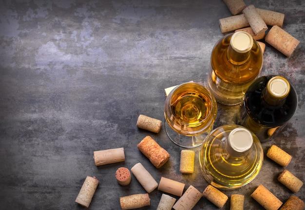 Bottiglie e vetro del vino bianco e rosso sulla tavola, con lo spazio della copia