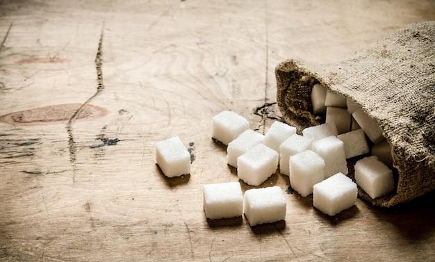 Zucchero bianco raffinato in borsa. sullo sfondo di legno.