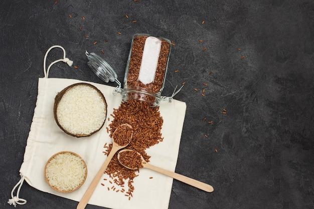 Riso bianco in guscio di noce di cocco riso rosso in barattolo di vetro cucchiai di legno su riso rosso sacchetto di imballaggio di lino copia spazio piatto sfondo nero laici