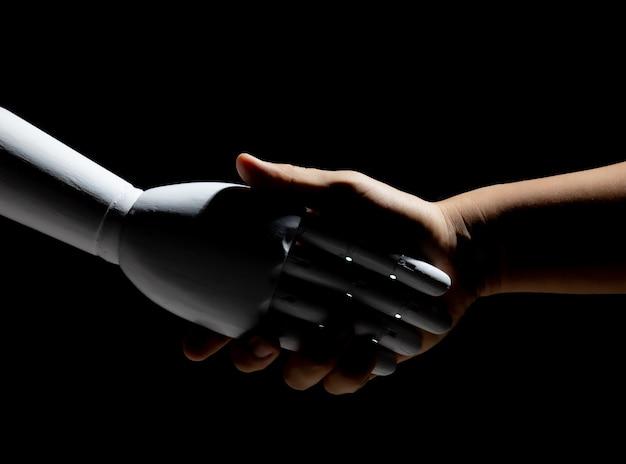 Stretta di mano del robot bianco con umano isolato su sfondo nero