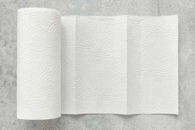 Rotolo bianco di asciugamani di carta per uso domestico su sfondo grigio, profondità di nitidezza ridotta