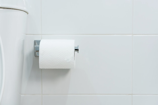 Un rotolo bianco di carta igienica morbida che appende ordinatamente sul supporto cromato su una parete bianca del bagno. avvicinamento