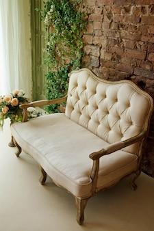 Stanza bianca con divano rosa, fiori vicino alla finestra nel soggiorno retrò