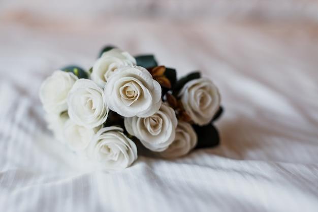 Secchio di fiori di rosa bianca su letto bianco