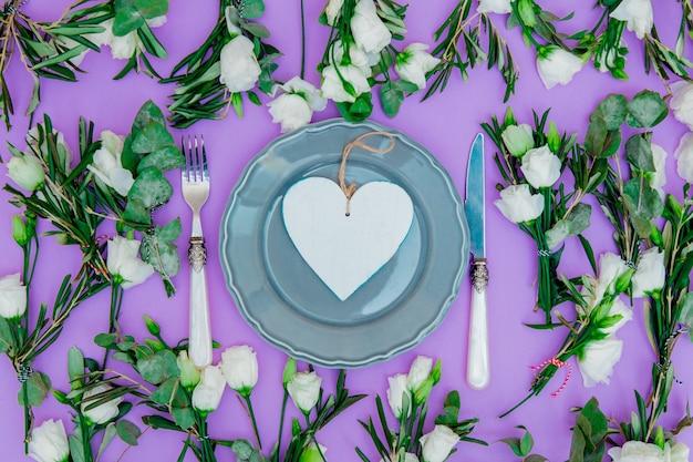 Rose bianche e piatti su sfondo viola. sopra la vista