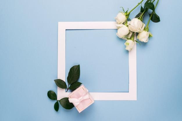 Rose bianche e cornice bianca presente decorata con foglie fresche su sfondo blu