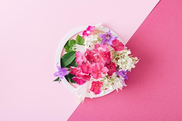 Cornice rotonda bianca con fiori rosa e foglie verdi su sfondo rosa. disposizione piatta. composizione minimalista estiva e primaverile.