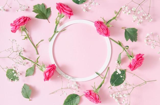 Cornice rotonda bianca con rose rosa su sfondo rosa. composizione di arte floreale minimalista