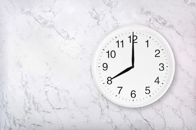 Orologio da parete rotondo bianco su sfondo di marmo. otto in punto.
