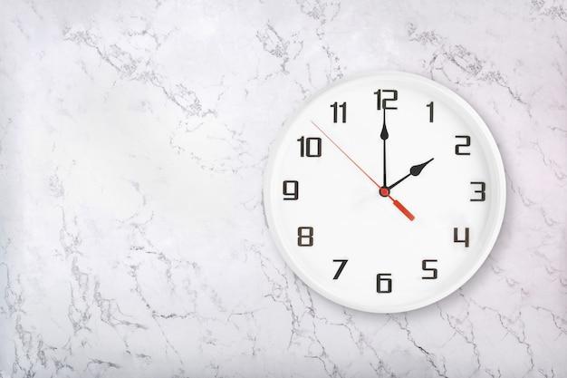 Orologio da parete rotondo bianco su sfondo di marmo