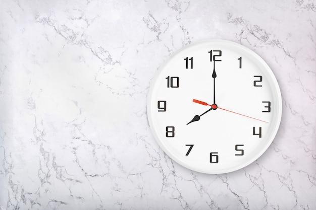 Orologio da parete rotondo bianco su sfondo di marmo naturale bianco. otto in punto