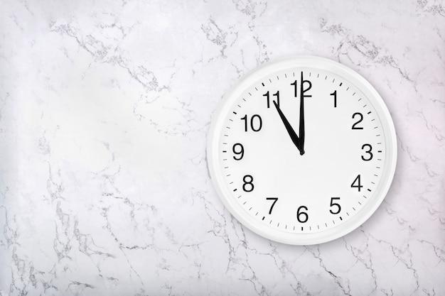 Orologio da parete rotondo bianco su sfondo di marmo naturale bianco.