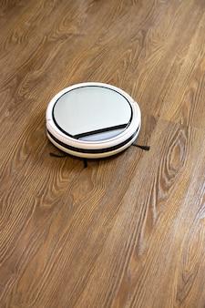 Aspirapolvere robot senza fili rotondo bianco su pavimento in laminato marrone