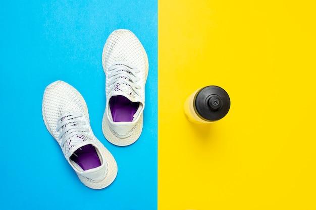 Scarpe da corsa bianche e una bottiglia di acqua su un fondo giallo e blu astratto. concetto di corsa, allenamento, sport.