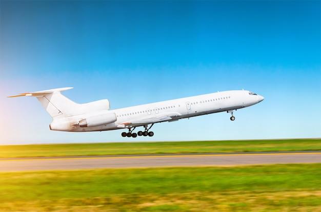 L'aeroplano russo bianco decolla all'aeroporto contro uno sfondo di cielo limpido.