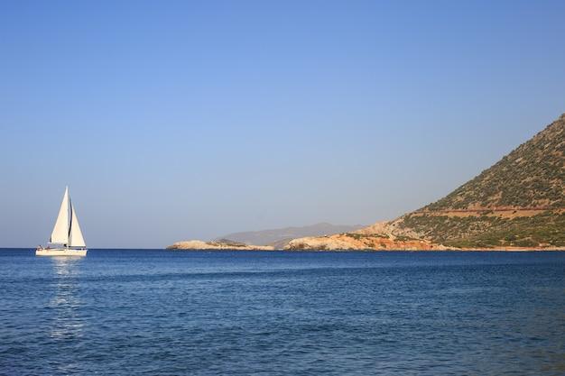 Barca a vela bianca nel mar mediterraneo aperto in una giornata di sole