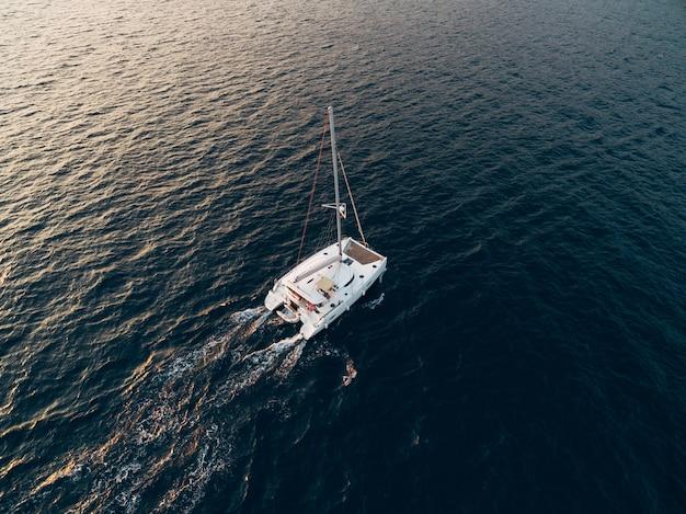 L'yacht del catamarano a vela bianco naviga nel mare blu